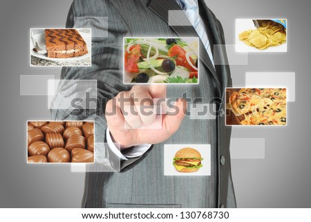 Businessman pushes touch screen button with salad on virtual interface with food. Diet concept
