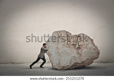 Businessman pushing a boulder  - stock photo