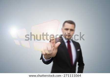 businessman pushing a button on a touch screen interface.