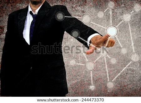businessman pushing a touch screen interface in the old texture - stock photo