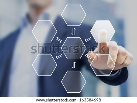 Businessman pushing a virtual hexagonal button with office buildings in background - stock photo