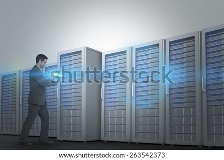 Businessman pushing against three digital grey server towers