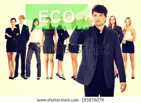 Businessman pushing ECO on a touch screen interface. Business team at background - stock photo