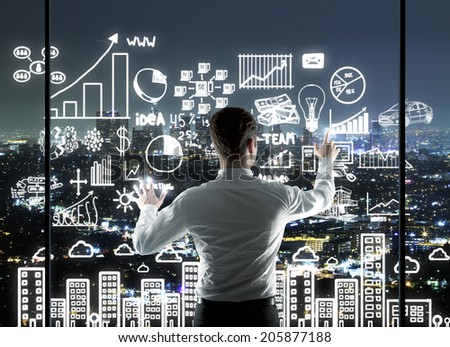 businessman pushing interface in night office - stock photo