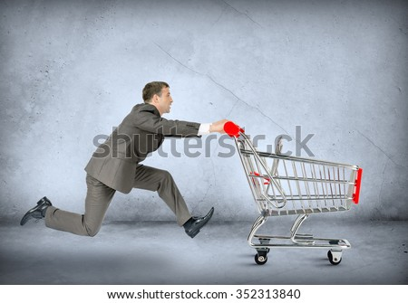 Businessman pushing shopping cart on grey wall background - stock photo