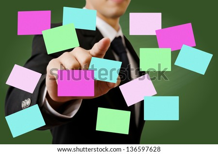 Businessman pushing sticky note on the whiteboard.