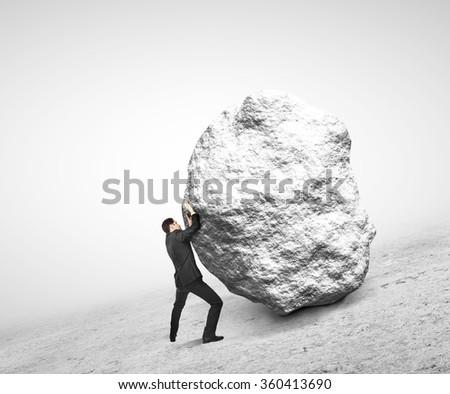 businessman pushing stone up on hill - stock photo