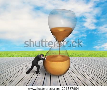 businessman pushing tilt sandglass on wooden floor with nature sky - stock photo