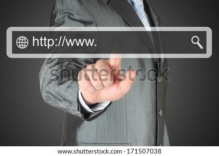 Businessman pushing virtual search bar on dark background, internet concept  - stock photo
