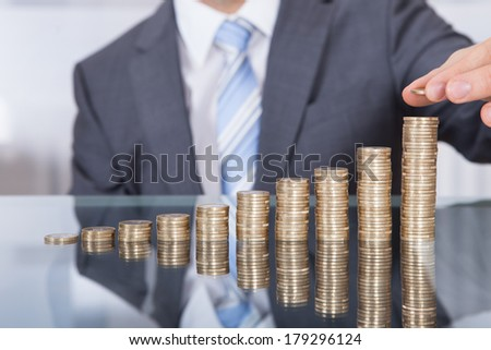 Businessman Put Coin To Highest Stack Of Coins - stock photo