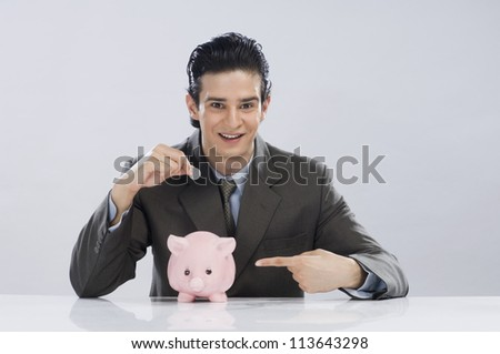 Businessman putting a coin into a piggy bank - stock photo