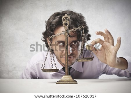 Businessman putting a coin on a balance