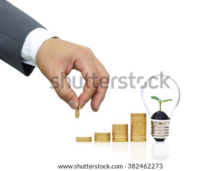 Businessman putting a coin to a stack of golden coins arranged as a graph with a green plant growing on a light bulb - Green saving concept for wealth and environment