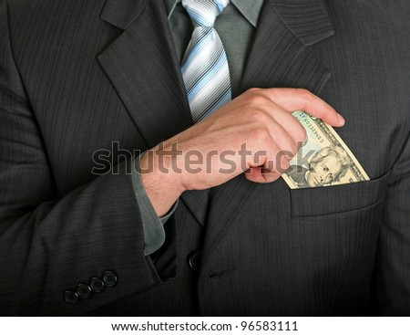 Businessman putting a dollar bill in his pocket - stock photo
