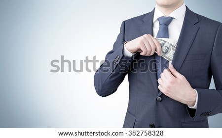 businessman putting a one-hundred dollar banknote into the chest pocket. Grey background. Front view, no head. Concept of getting money. - stock photo