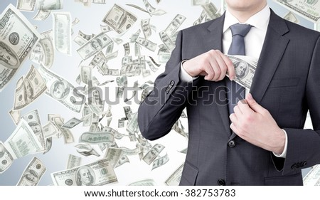 businessman putting a one-hundred dollar banknote into the chest pocket. Money flying at the background. Front view, no head. Concept of getting money.