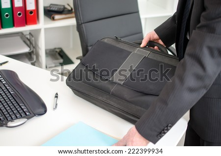 Businessman putting his laptop suitcase on his desk