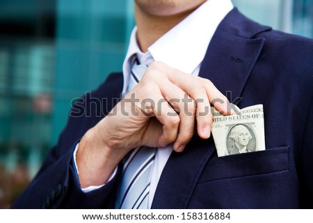 Businessman putting money in his pocket - stock photo