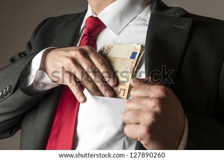Businessman putting money in his shirt pocket - stock photo