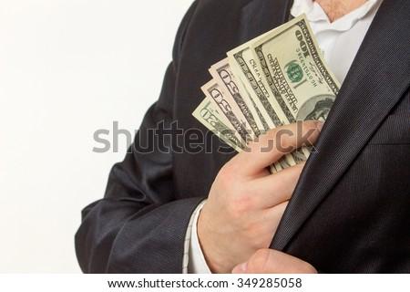 Businessman putting money in suit jacket pocket - stock photo