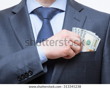 Businessman putting money in the breast pocket, closeup shot