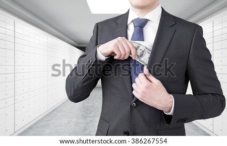 Businessman putting one hundred dollar banknotes into the chest pocket. No head seen. Underground crossing at background. Concept of getting money. - stock photo