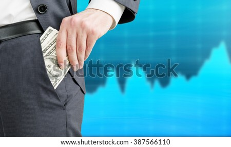 Businessman putting one hundred dollar banknotes into the pocket. Only trousers seen. Blue graphs at background. Concept of getting money. - stock photo