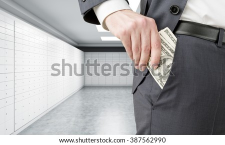 Businessman putting one hundred dollar banknotes into the pocket. Only trousers seen. Dollars at background. Concept of getting money. - stock photo