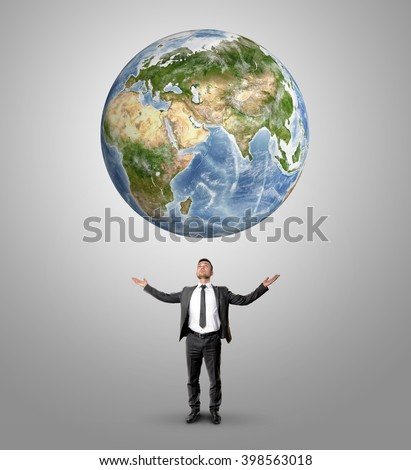 Businessman raised his hands to hold Earth looking at it. Elements of this image are furnished by NASA - stock photo