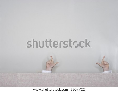 Businessman raises his hands above the office cubicle in a sign of success with his fingers out
