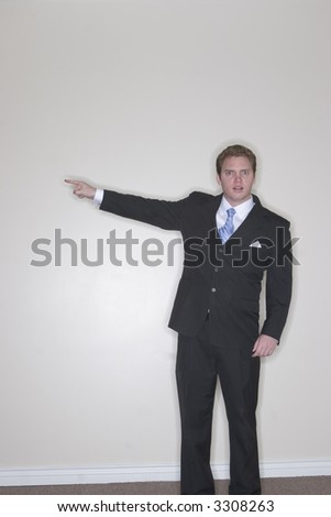 Businessman raising his arm and pointing out to the left with his hand in his business suit