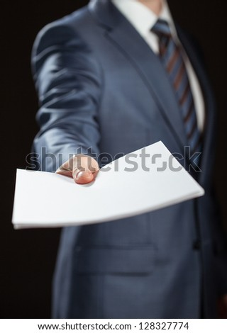Businessman reaching out documents to you on black background - stock photo