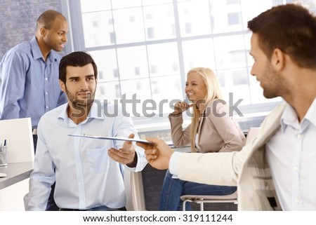 Businessman reaching out for folder handed by colleague. - stock photo