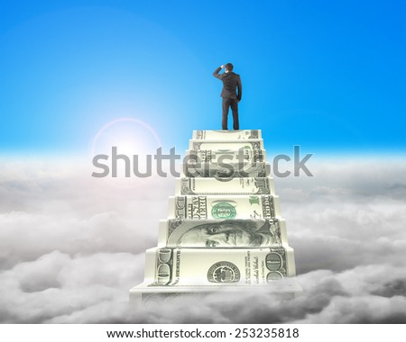 Businessman reaching the top of money stairs looking around blue sky with sunlight cloudscape background - stock photo