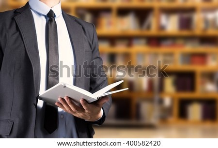 Businessman reading a book in Library room blur background - stock photo