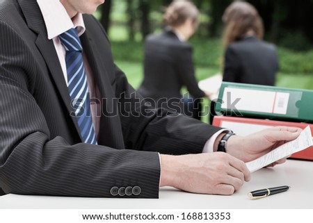 Businessman reading a document and two business womans in background