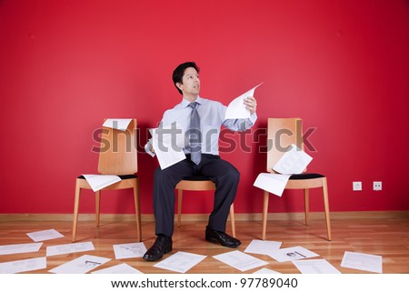 Businessman reading a document in a messy office full of papers on the floor - stock photo