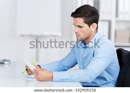 Businessman reading a document while sitting at his desk in the office looking at it with a serious expression - stock photo