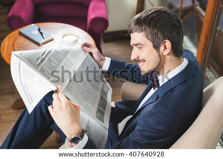 Businessman reading a newspaper at cafe, mourning. Daily news. Good news! Job search - stock photo