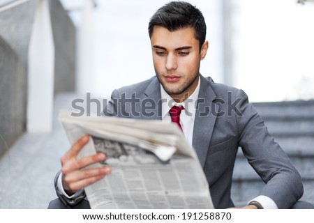 Businessman reading a newspaper in an urban environment