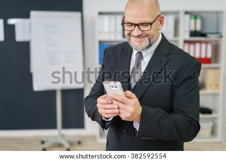 Businessman reading a text message on his mobile phone with a pleased satisfied smile as he stands in the office - stock photo