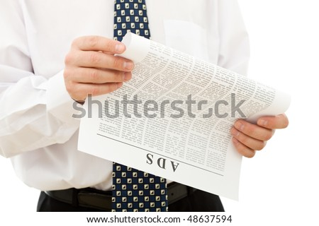 Businessman reading ads from the paper - isolated