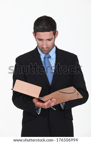 Businessman reading contents of folder - stock photo