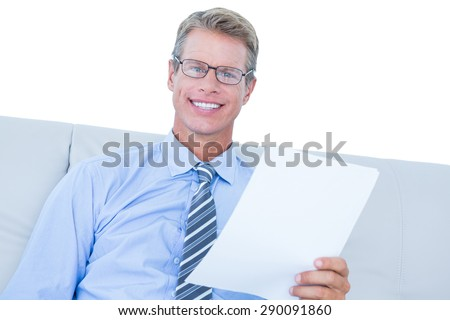Businessman reading document at his desk against white wall