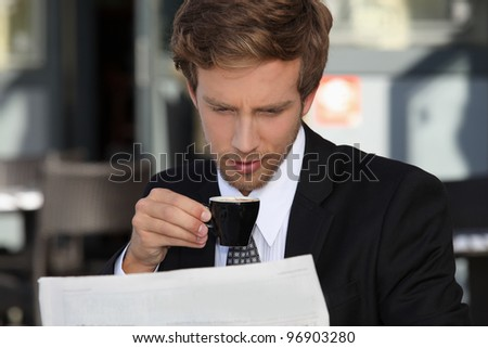 Businessman reading documents and drinking expresso - stock photo