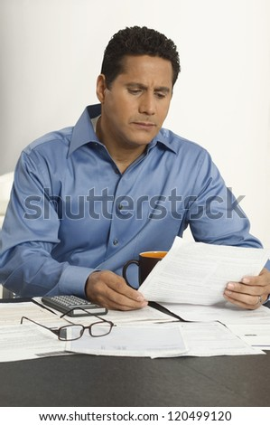 Businessman reading documents at desk in office