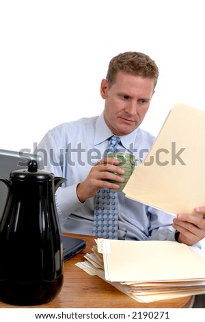 Businessman reading files and drinking coffee