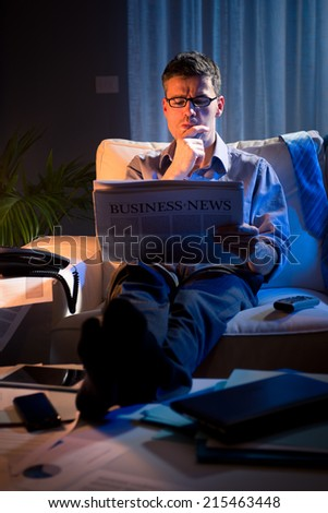 Businessman reading financial newspaper late at night sitting on sofa. - stock photo