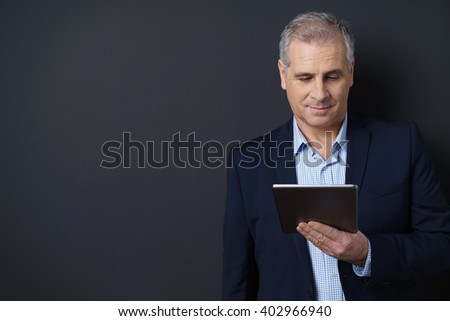 Businessman reading from a handheld tablet computer with a quiet smile over a dark background with copy space - stock photo