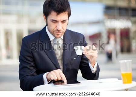 Businessman reading his digital tablet during breakfast - stock photo